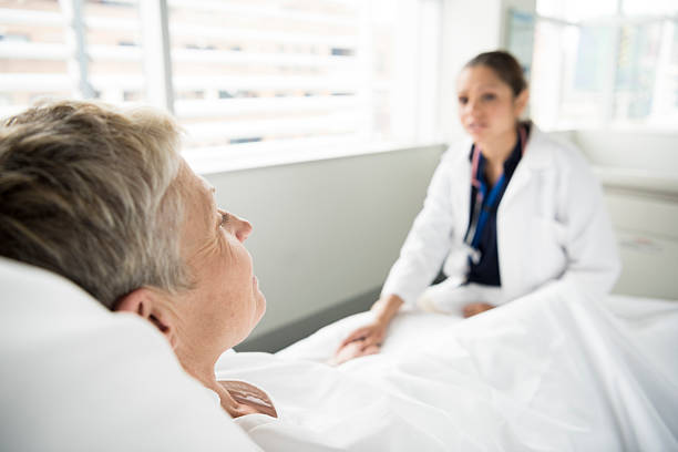 Senior female patient in hospital bed with doctor in background picture id503764432?b=1&k=6&m=503764432&s=612x612&w=0&h=ryskqkcz0yy6h314xbaevu7yvmquudnsfd9fhubg0ps=