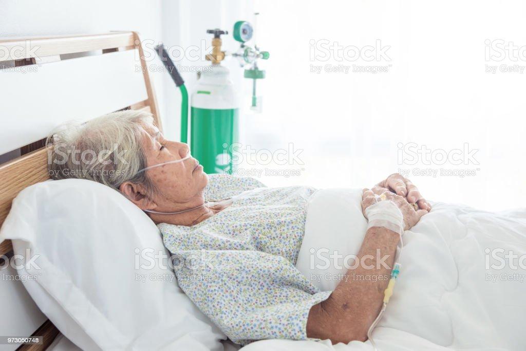 senior female patient sleeping on bed stock photo