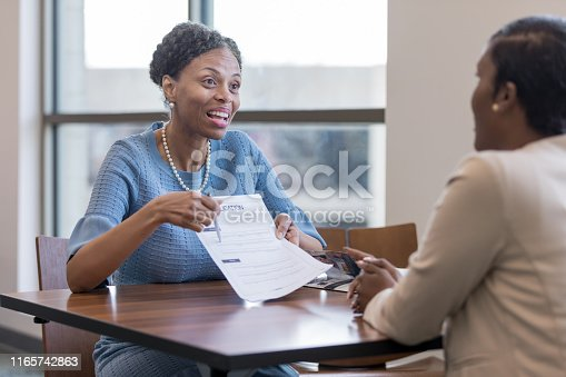 istock Senior female personal banker shows client account application 1165742863