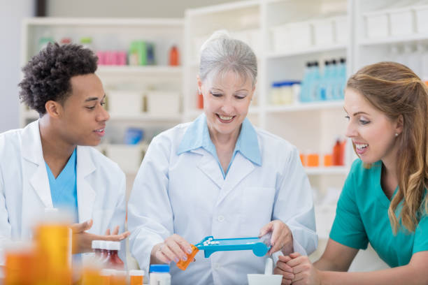 senior female pharmacist demonstrates compounding to young coworkers - pharmaceutical compounding stock photos and pictures