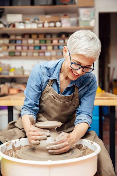oleiro fêmea sênior que trabalha na roda da cerâmica ao sentar-se em sua oficina - cerâmica artesanato - fotografias e filmes do acervo