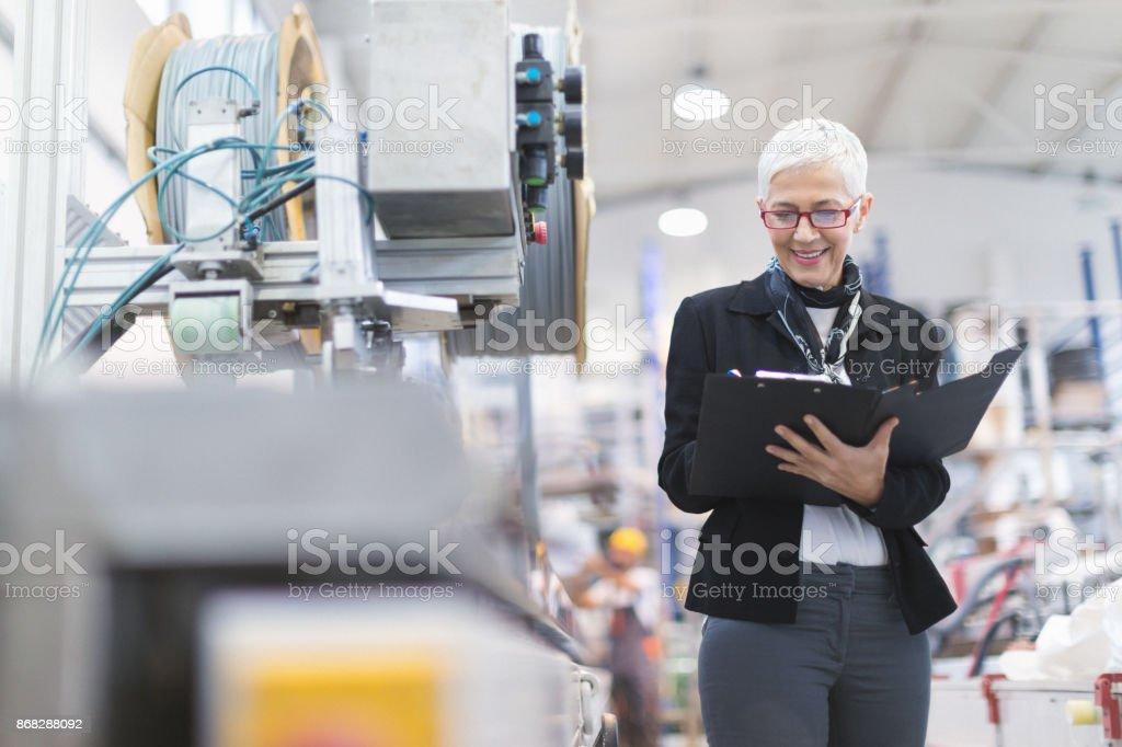 Senior female quality inspector at factory stock photo