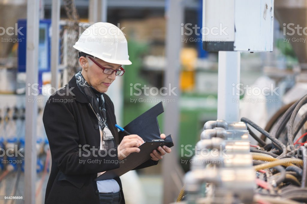 Senior female quality inspectors in high tech factory stock photo