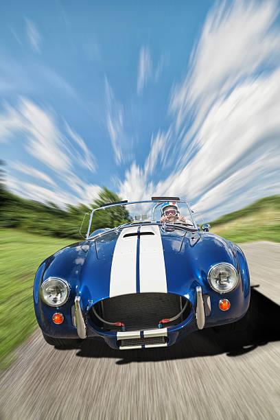 senior female racing down road - alten muscle cars stock-fotos und bilder