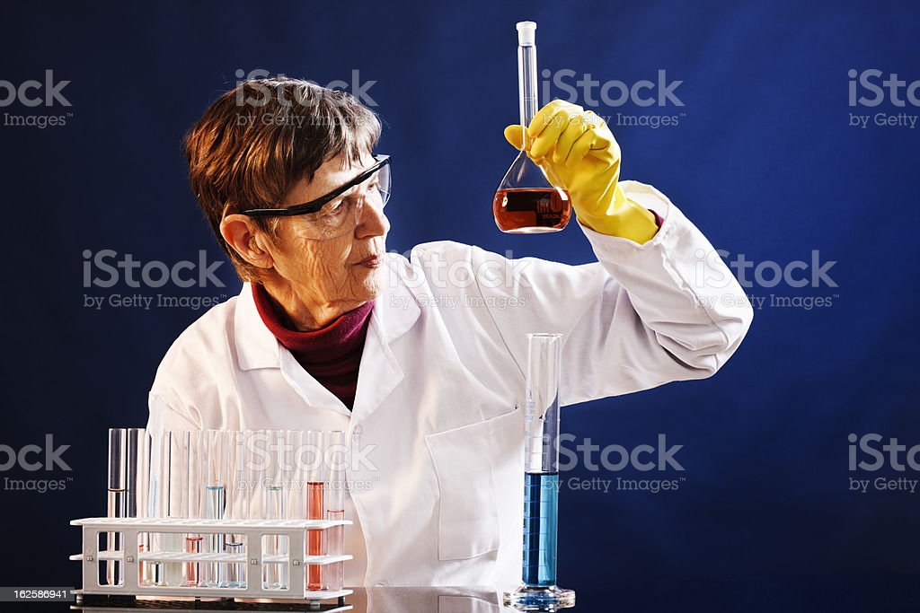 Senior female scientist studies contents of flask in laboratory stock photo