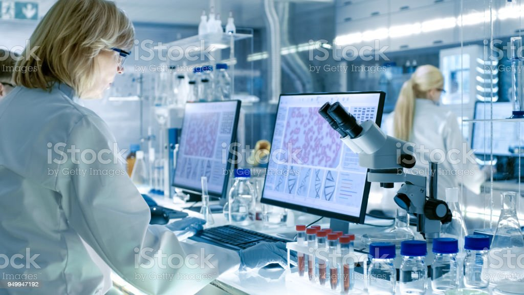 Senior Female Scientist Works with High Tech Equipment in a Modern Laboratory. Her Colleagues are Working Beside Her. stock photo