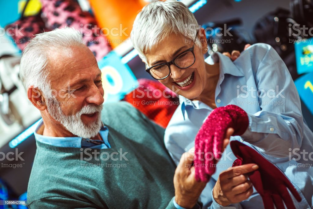 Senior female showing a pair of sparkly crimson red gloves to her...