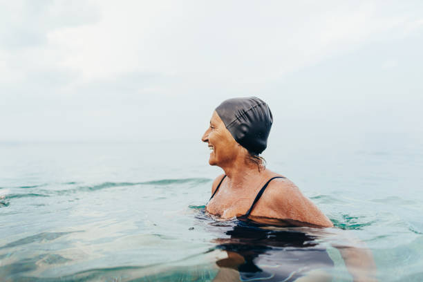 Senior female swimmer in the sea stock photo
