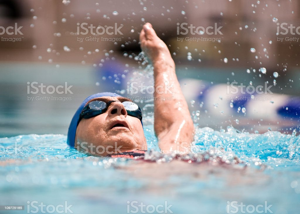 Senior female swimming stock photo