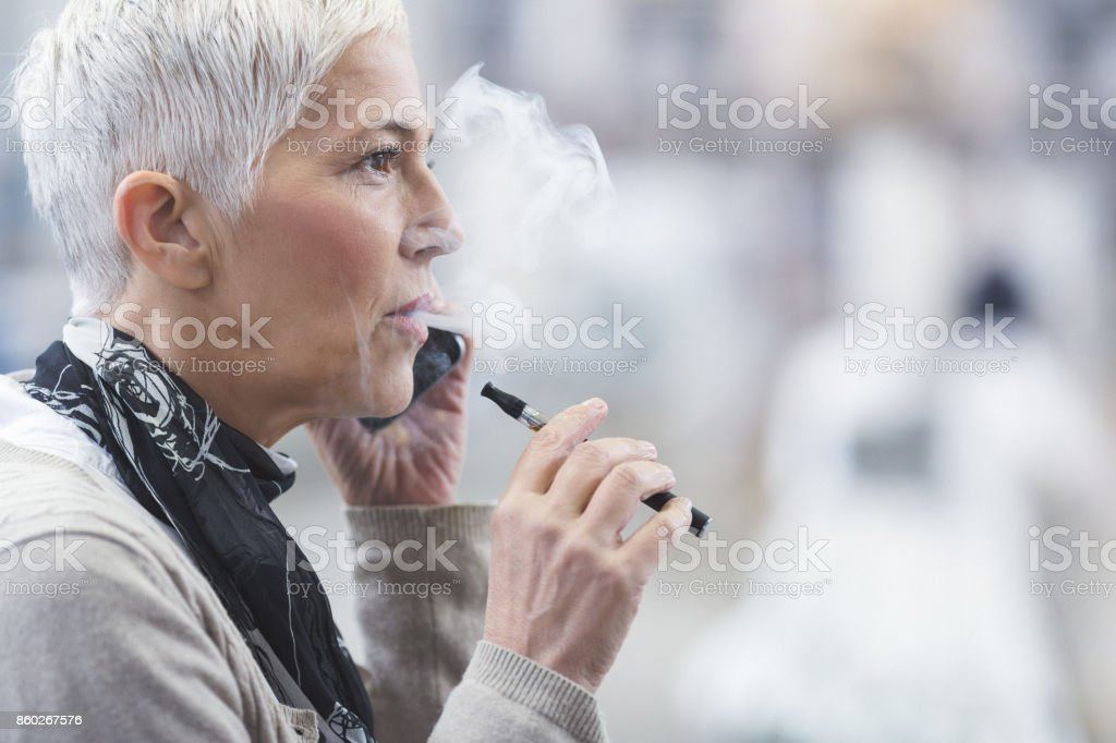 Senior female using electronic cigarette stock photo