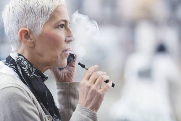 Senior weiblichen Verwendung elektronische Zigarette – Foto