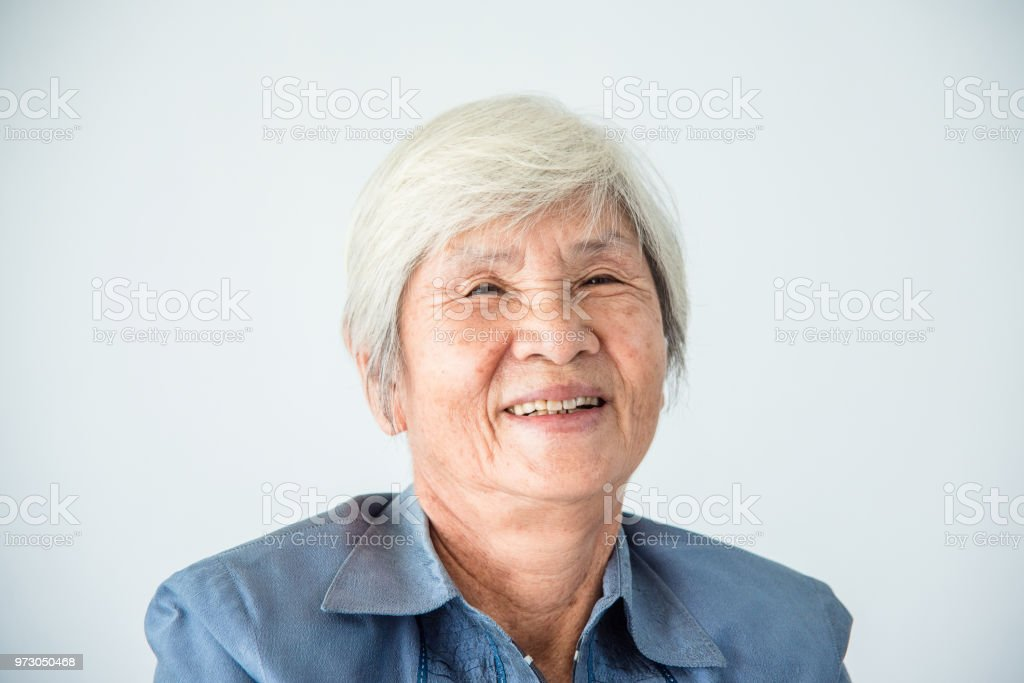 senior female with white color hair smiling at camera stock photo
