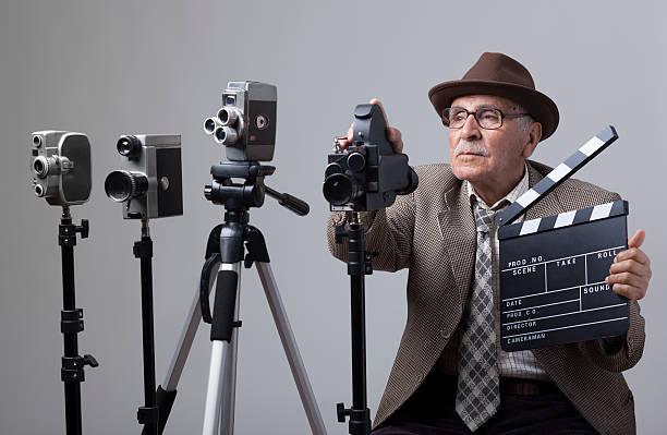 senior film director hinter die kamera. - klappe hut stock-fotos und bilder