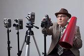 istock Senior Film director behind camera 477888385