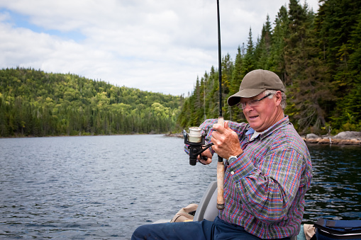 115874504 istock photo Senior Fisherman Catching a Fish 157636135