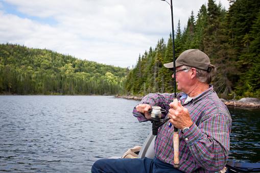 115874504 istock photo Senior Fisherman Catching a Fish 157636136