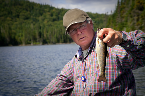 115874504 istock photo Senior Fisherman Catching a Fish 157649065