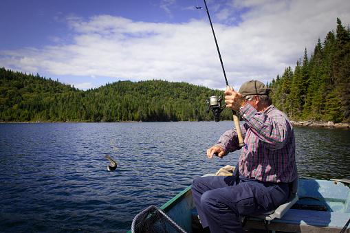 115874504 istock photo Senior Fisherman Catching a Fish 182861091