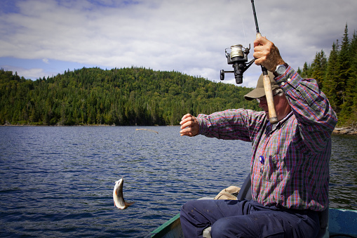115874504 istock photo Senior Fisherman Catching a Fish 182927257