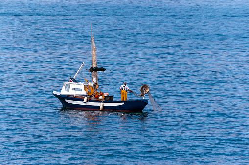Senior fisherman on a small Fishing Boat - Liguria Italy