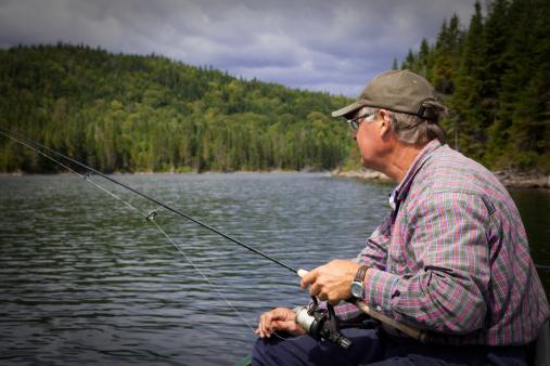 115874504 istock photo Senior Fisherman on Lake in Summer 157636307