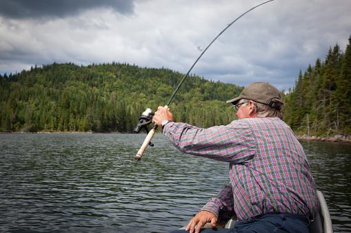 115874504 istock photo Senior Fisherman on Lake in Summer 182862014