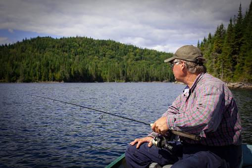 115874504 istock photo Senior Fisherman on Lake in Summer 182917116