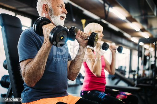 Mature fit man and woman doing exercises in gym to stay healthy