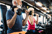 istock Senior fit man and woman doing exercises in gym to stay healthy 1084046810