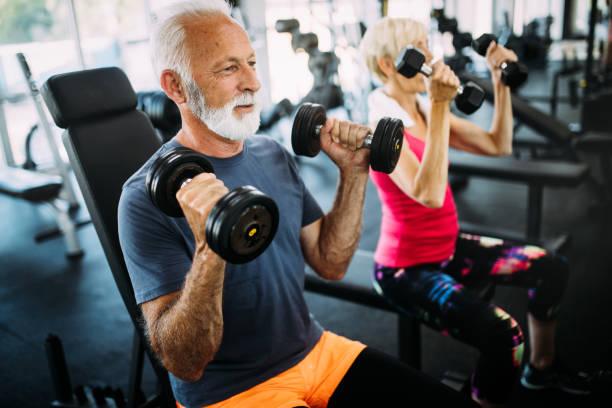 senior fit man och kvinna gör övningar i gymmet för att hålla sig frisk - active senior bildbanksfoton och bilder