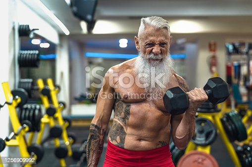 Senior fitness man doing biceps curl exercises inside gym - Fit mature male training with dumbbells in wellness club center - Body building and sport healthy lifestyle concept