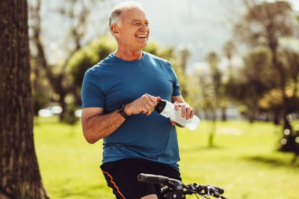 seniorenfitness mann trinkwasser - einzelner senior stock-fotos und bilder