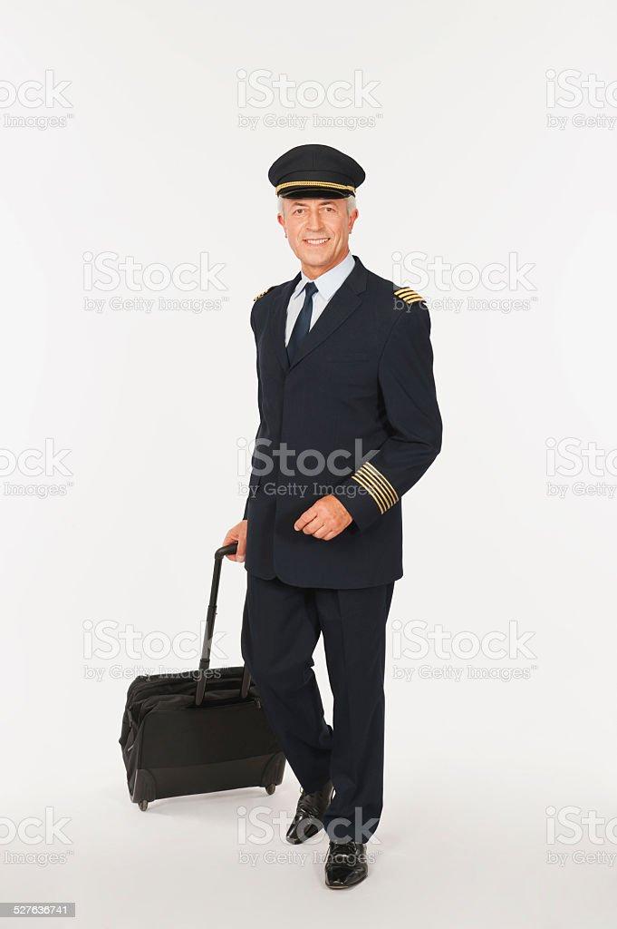 Senior flight captain carrying luggage on white background stock photo