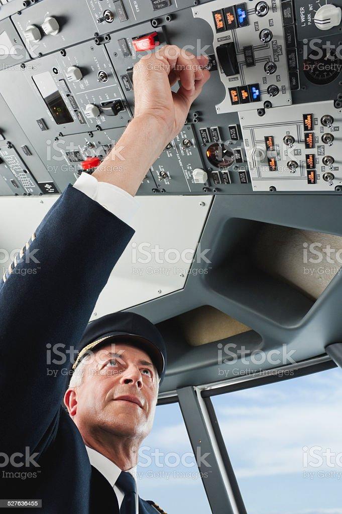 Senior flight captain turning switch in airplane cockpit stock photo