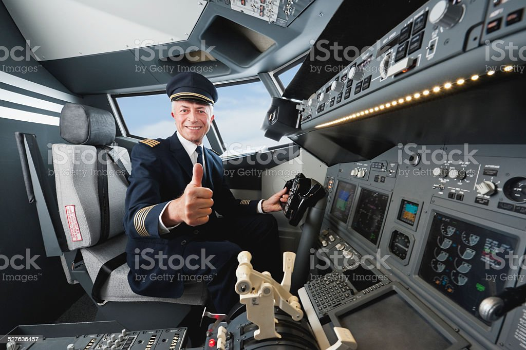 Senior flight captain with thumbs up in airplane cockpit stock photo
