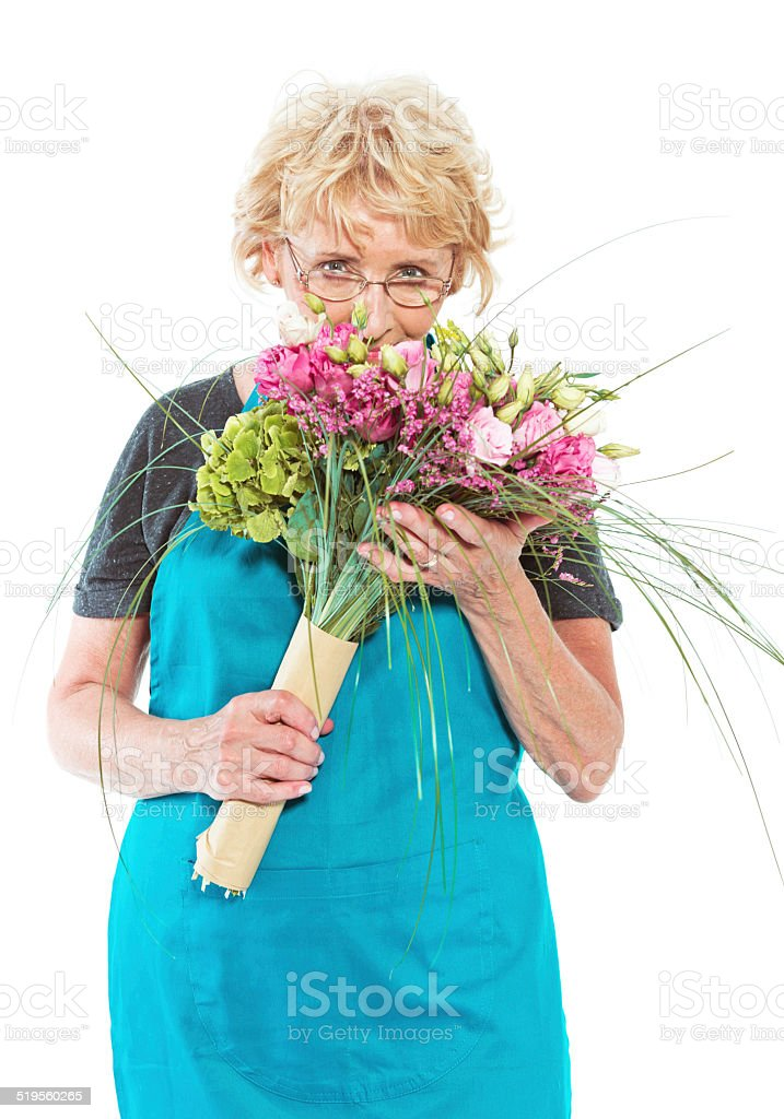 Senior florist with flowers on white background Cheerful senior florist holding bouquet in hands, looking at the camera. Studio shot, white background. 60-64 Years Stock Photo