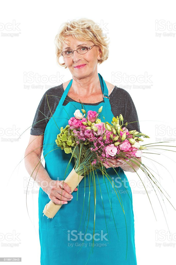 Senior florist with flowers on white background Cheerful senior florist holding bouquet in hands and smiling at the camera. Studio shot, white background. 60-64 Years Stock Photo