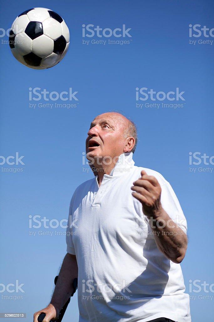 Senior football player with walking stick stock photo