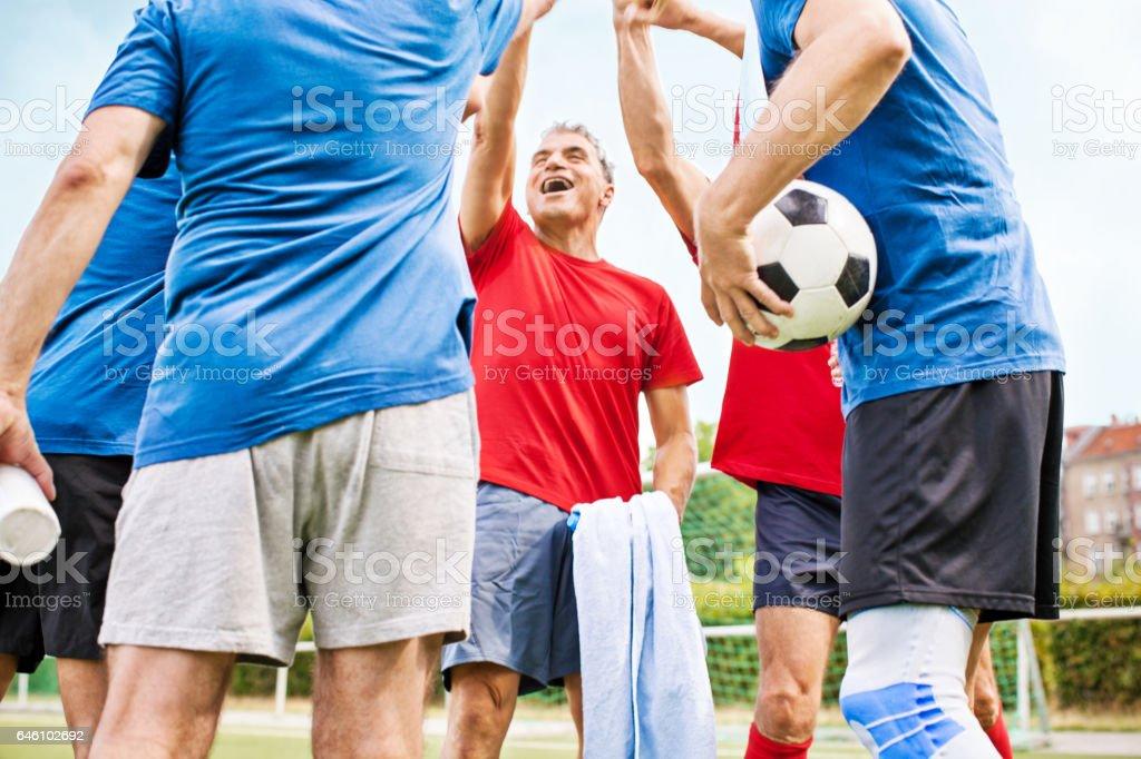 Senior football players cheering stock photo
