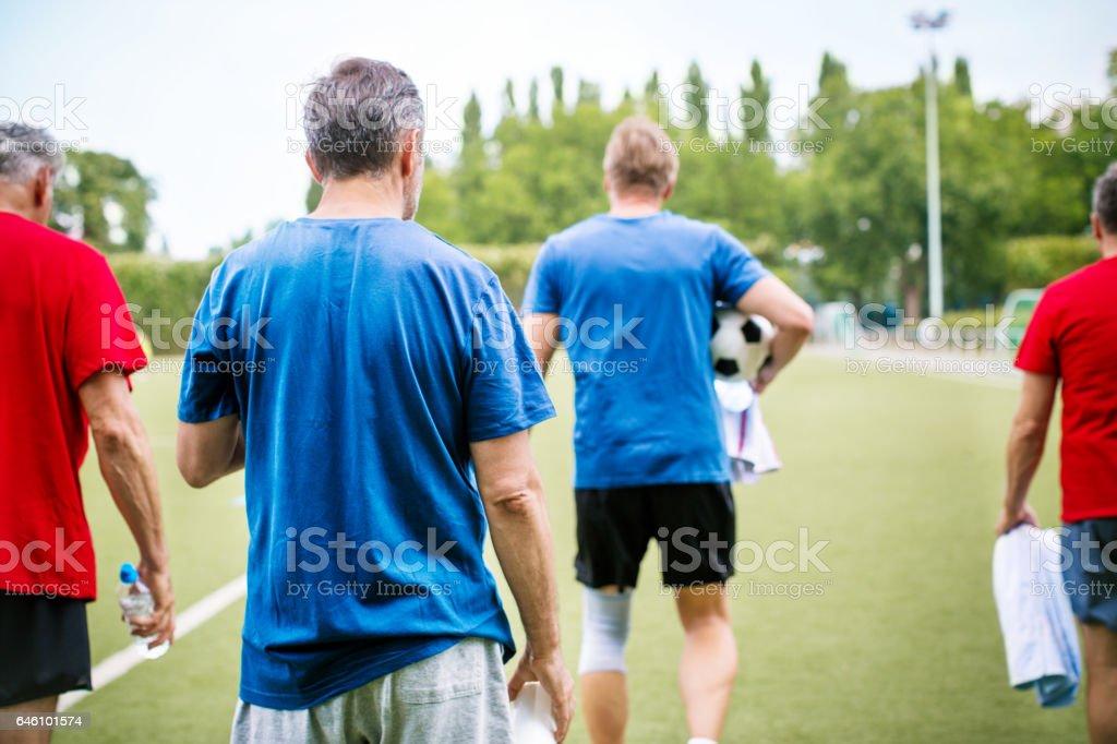 Senior football players walking on the soccer field stock photo