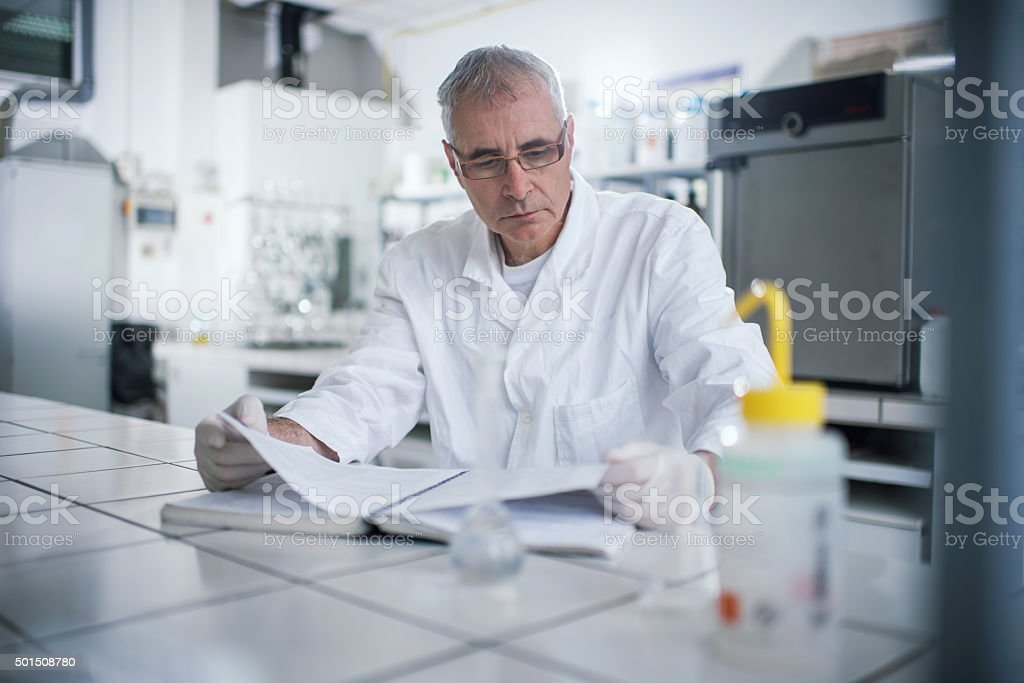 Senior forensic scientist reading medical data in laboratory. stock photo