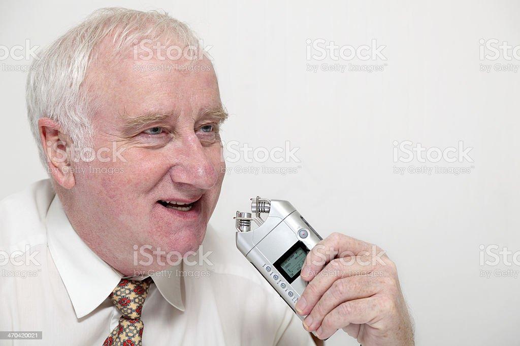 senior formal businessman uses digital recorder for dictation recording stock photo