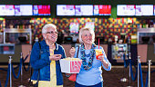 Two multi-ethnic senior women having fun together going to see a movie at the theater. They are carrying popcorn and drinks from the concession stand, smiling and walking. The Hispanic woman wearing eyeglasses is in her 60s and her friend is in her 70s.