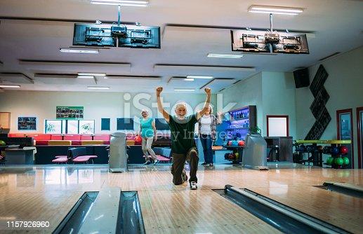 Group of seniors having fun bowling.