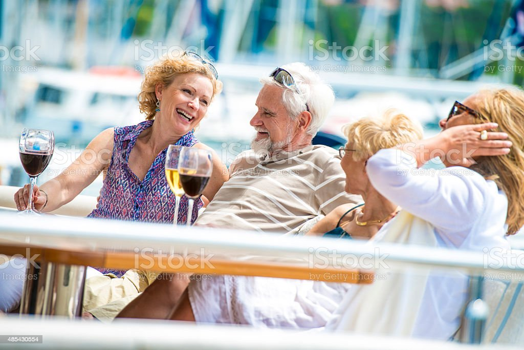 Senior friends on a yacht in a marina, sitting behind table, drinking...