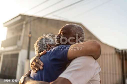 Senior friends greeting each other on the street