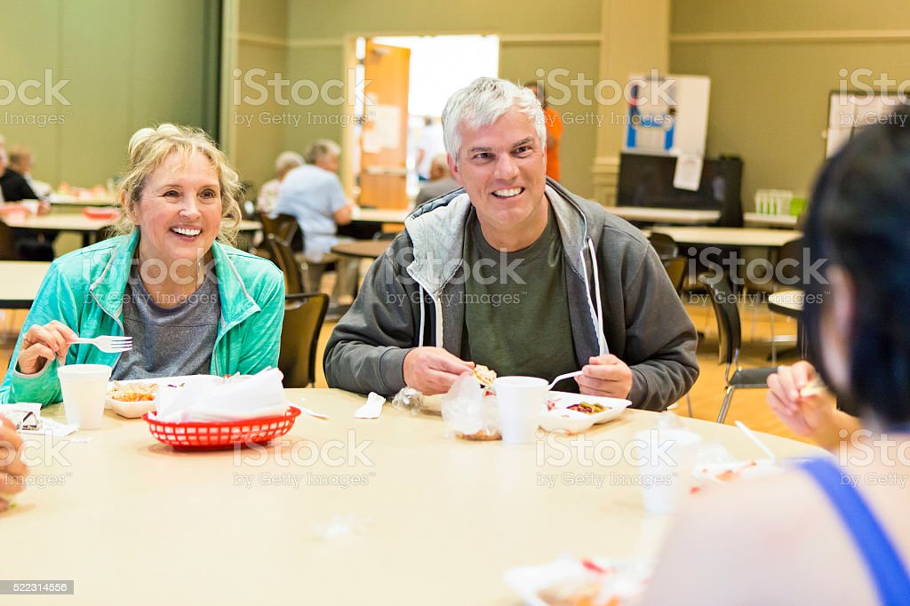 Senior friends have lunch at fitness center cafe stock photo