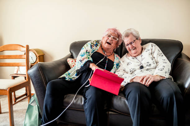 Senior Friends Having a Good Laugh Two senior woman sitting chatting in a nursing home in North East of England. One has pink hair. They are sitting on a sofa having a good laugh. One woman is wearing a nasal oxygen cannula. Another lady has a personal alarm GPS tracker around her neck medical oxygen equipment stock pictures, royalty-free photos & images