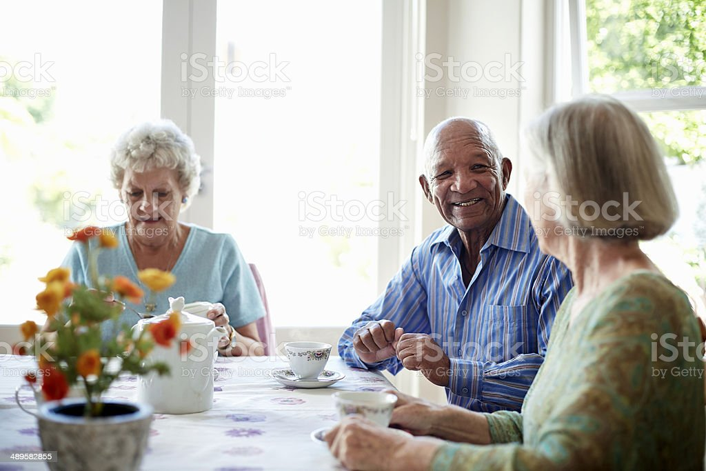 Happy senior friends having breakfast at table in nursing home