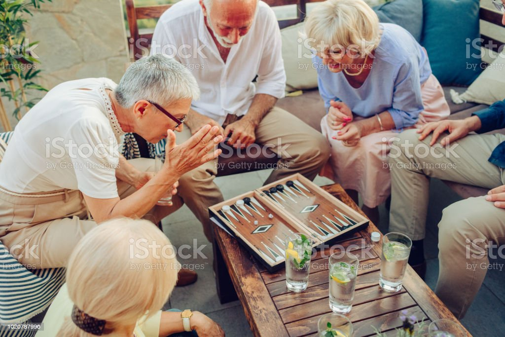 Senior Friends Playing Backgammon stock photo